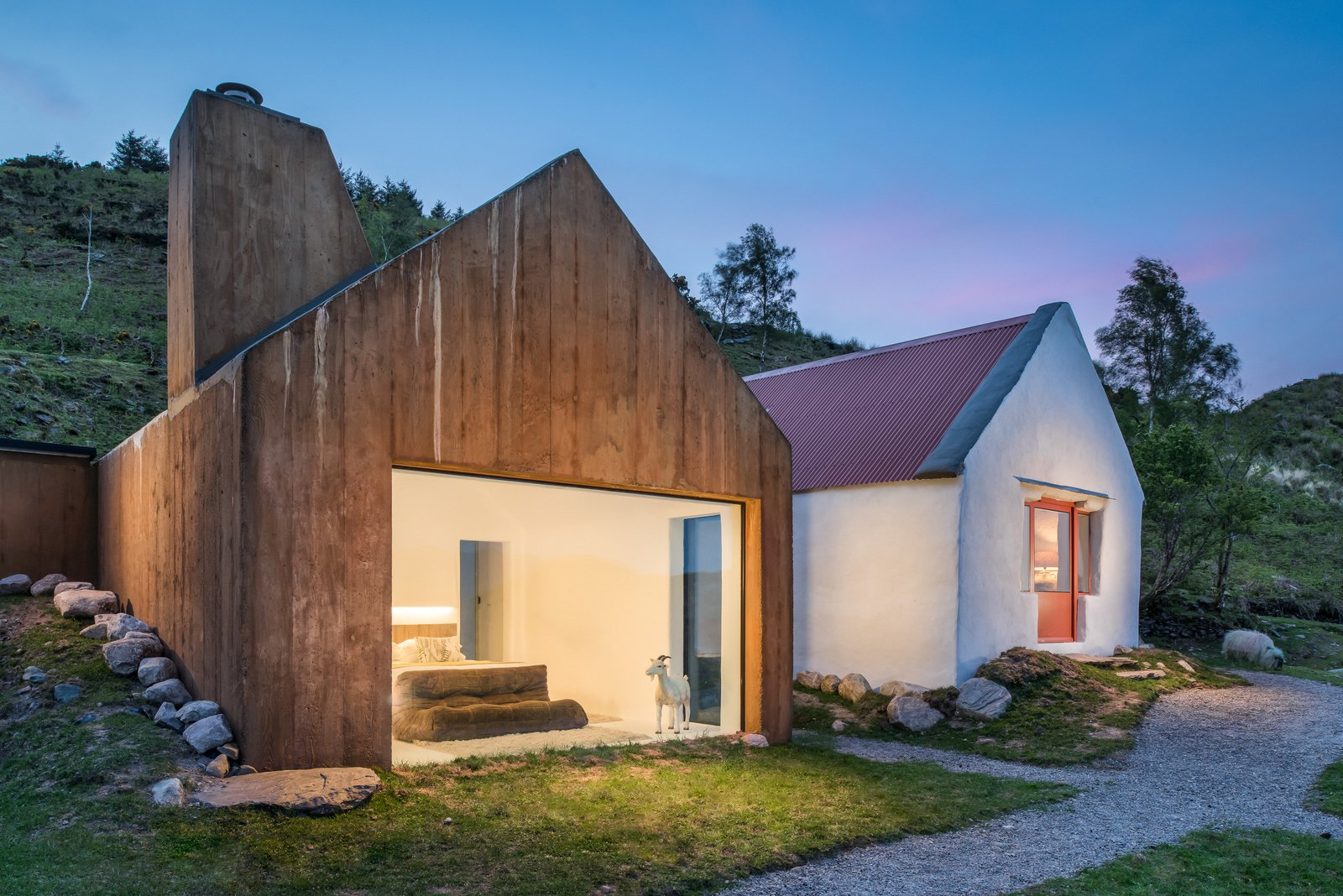 This cute cottage near the remote County Kerry lakeside town of Treangarriv has a modern poured concrete extension that mimics the original adjoining cottage. The color of the wood grain oxidized concrete matched the mountains in the background and helps the extension blend seamlessly into the landscape. The bathroom has a glass roof so guests can gaze up at the stars from a sunken bathtub. Tagged: Exterior, House, and Wood Siding Material.  Best Photos from 9 Traditional-Turned-Modern Cottages You Can Rent in the UK
