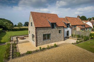9 Traditional-Turned-Modern Cottages You Can Rent in the UK - Photo 9 of 9 - When remodeling this 300-year-old cottage, architect Miljana Salinovic installed steel frames in order to preserve the texture of the traditional flint walls. A new extension was also added, which is clad in charred cedar.