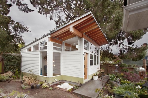 This Seattle studio shed that is sited on a plant-filled backyard is used by it's owners as a place to engage in their diverse passions – painting, sculpture, and gardening and collecting vintage furniture.