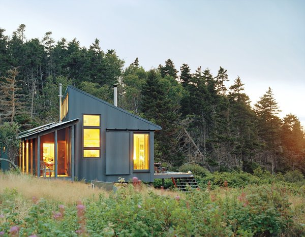 Writer and journalist Bruce Porter's off grid getaway on an island off the Maine coast, was designed by his architect daughter, who is the founder of her own practice Alex Scott Porter Design. Sited close to the water it has a screen porch was angled to capture direct southern exposure for the solar panels.