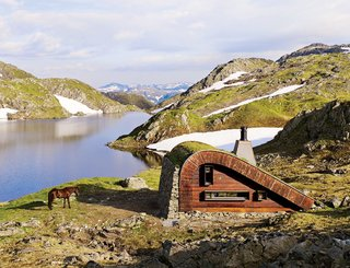 7 Prefabs Set in Nature - Photo 7 of 7 - Tucked away on the edge of a small lake surrounded by mountains and topped off with a grass-covered roof, this hunting cabin designed by Snøhetta is made with locally sourced stones. It's a prefab dream come true for nature lovers.