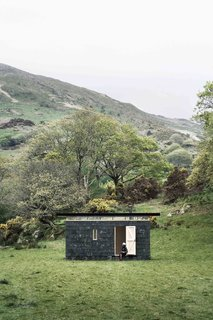 9 Small Studios Where Writers and Artists Can Get Creative - Photo 3 of 9 - With a facade made of recycled slate tiles that were reclaimed from nearby farms, this writer's retreat on the edge of Snowdonia National Park in Mid Wales offers not only plenty of solitude, but also natural inspiration, thanks to the lush green valleys and windswept hills of the Welsh countryside. It was designed by Sydney-based architecture firm TRIAS.