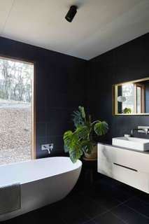 Dwell's Top 10 Bathrooms of 2017 - Photo 4 of 10 - A split monolithic form gives this modern residence its name—Two Halves House.<br>Distinguished by two pavilions that appear to stand apart at first sight—but are in fact connected—Two Halves House was designed with three requirements in mind. The homeowners wanted a high bush fire safety rating and a relaxed kitchen and living space for entertaining. Plus, they wanted to maximize the sloping site and the south-facing views.