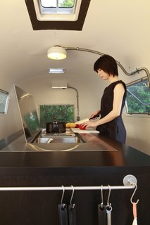 6 Modern Homes on Wheels - Photo 3 of 12 - Designing a series of foldaway furniture, Japanese architect Toshihiko Suzuki transformed a standard trailer into a home with a hidden kitchen and a dining table for six (that doubles as a bed at night).