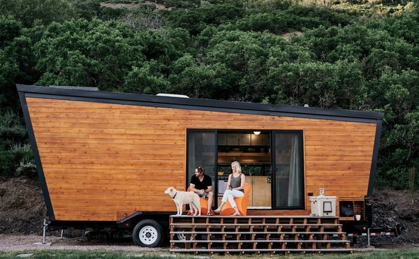 """Nicknamed """"Woody"""", this 236-square-foot trailer which has taken a young, upwardly-mobile couple from Austin, Texas, to the Rocky Mountains hamlet of Marble, Colorado. The trailer, which cost just around $50,000 to build has modern birch-veneer plywood fit outs and skylights, and accommodates a half-size refrigerator, eight-inch-deep storage compartments built into the floor, a loft bed and even a galvanized-steel cow trough bathtub."""