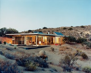 7 Incredible Prefab Homes You Can Rent For Your Next Holiday - Photo 2 of 7 - Los Angeles–based design partners Taalman and Koch created this house in Pioneertown, California, from prefabricated structural components, and included glass walls on which artists later applied surface graphics. Available for rent through Boutique Homes, this 1,100-square-foot house cost approximately $265,000 to build and is composed of a Bosch aluminum framing system and perforated steel decking roof. The interior floors are equipped with radiant heating, and cabinets were built out of Formica or plastic-laminated plywood.