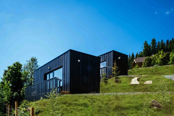 Four prefabricated alpine micro-houses by COMMOD-Haus were added to art-lodge – a boutique hotel in Carinthia, Austria. The transportable and environmentally friendly timber frame structures were delivered to their designated spot at the end of a winding mountain road and mounted securely with ground screws. The houses were assembled within hours and the only part that was built on ute was the terrace. Part of the farmhouse hotel complex, guests in the 248-square-foot micro-houses can use all of the hotel's facilities.