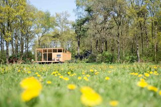 7 Incredible Prefab Homes You Can Rent For Your Next Holiday - Photo 6 of 7 - Overlooking a peaceful meadow in the province of Overijssel in the Netherlands is a snug, 452-square-foot prefabricated wooden hut with large windows that blur the boundaries between indoor and outdoor spaces. Build in two modules that were transported and assembled on site, the house, which was constructed mainly with Oregon pine, arrived complete with bathroom, kitchen, couches, table, inner walls, cabinets, beds, and floors. Custom-designed furniture, such as a sofa integrated into a sunken living area, and a U-shaped corner bench, imbues this little hut with plenty of quirky charm.