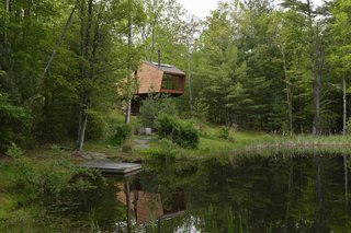 Enjoy the Rest of Fall by Renting One of These Cozy Cabins or Tree Houses - Photo 5 of 17 - Set amidst a densely forested 14-acre property on the edge of a natural swimming pond in Willow, this tree house in Upstate New York is a wonderful place for a fall retreat.  Just a two-hour drive from NYC, the house is clad in reclaimed-FSC timber and has a spacious lofted bedroom and open-plan lounge that opens out to two balconies on either side.
