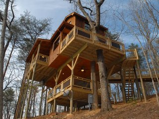 "Enjoy the Rest of Fall by Renting One of These Cozy Cabins or Tree Houses - Photo 12 of 17 - Located in the Aska Adventure area of Blue Ridge, Georgia, this 750-square-foot, three-story tree house called ""Canopy Blue"" has close to 1,200 square feet of outdoor deck and is great for families with kids. The house has high ceilings, French doors that overlook a fire pit below, a table crafted from a hollowed tree trunk, bunk beds, and a loft with a swing bed."