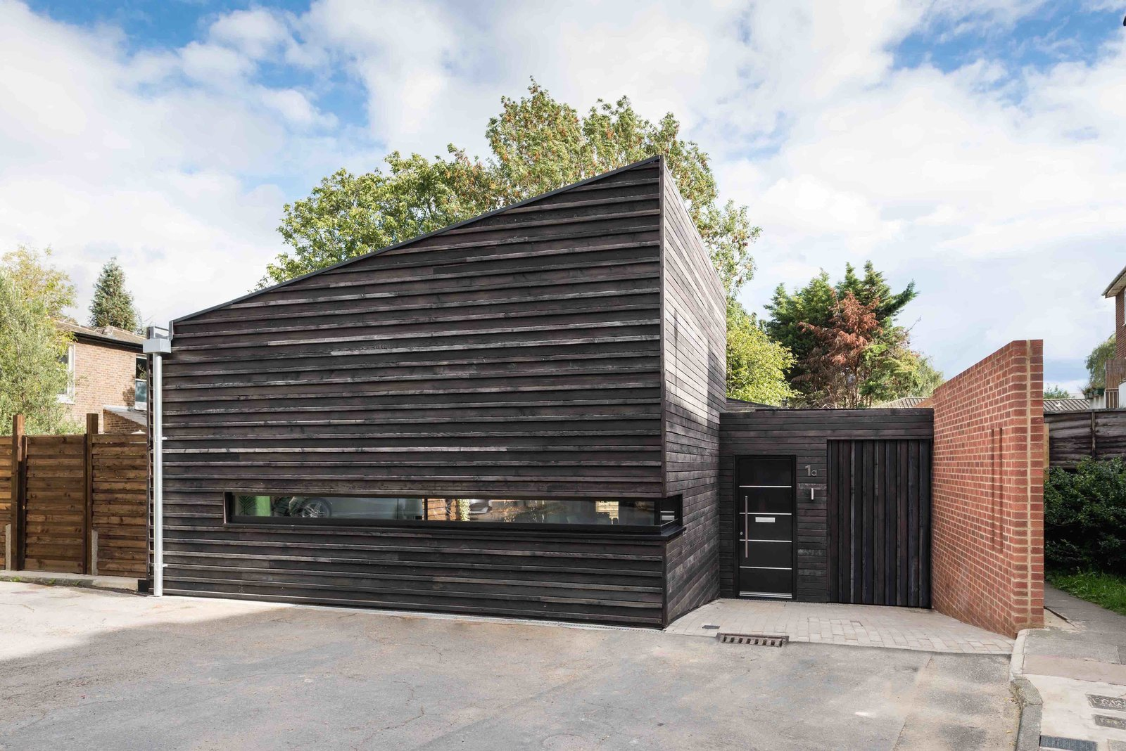 Located on a site where two obsolete garages formerly stood is a 935-square-foot prefab home in London's borough of Richmond.   Designed by London-based practice RDA Architects in collaboration with prefab and modular builders Boutique Modern, the building is clad in Shou Sugi Ban timber with fit-outs selected by the owner. Tagged: Exterior, Wood Siding Material, and Prefab Building Type.  Photo 4 of 10 in Dwell's Top 10 Prefabs of 2017 from This London Prefab Made of 7 Modules Was Raised in Just One Day