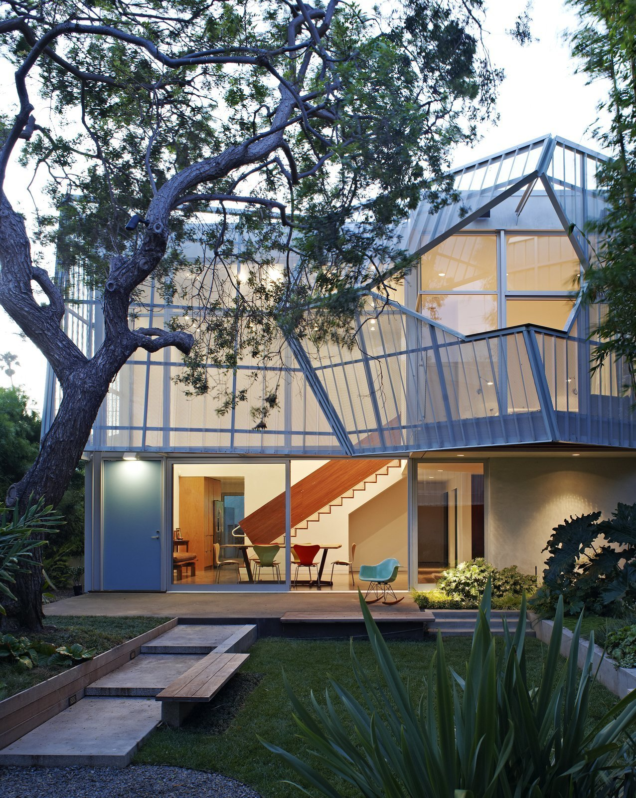 Kevin Daly Architects created a geometric perforated, folding metal skin supported by an aluminum exoskeleton, which shades the two-story glazed courtyard-facing façade of this home in Venice, California.