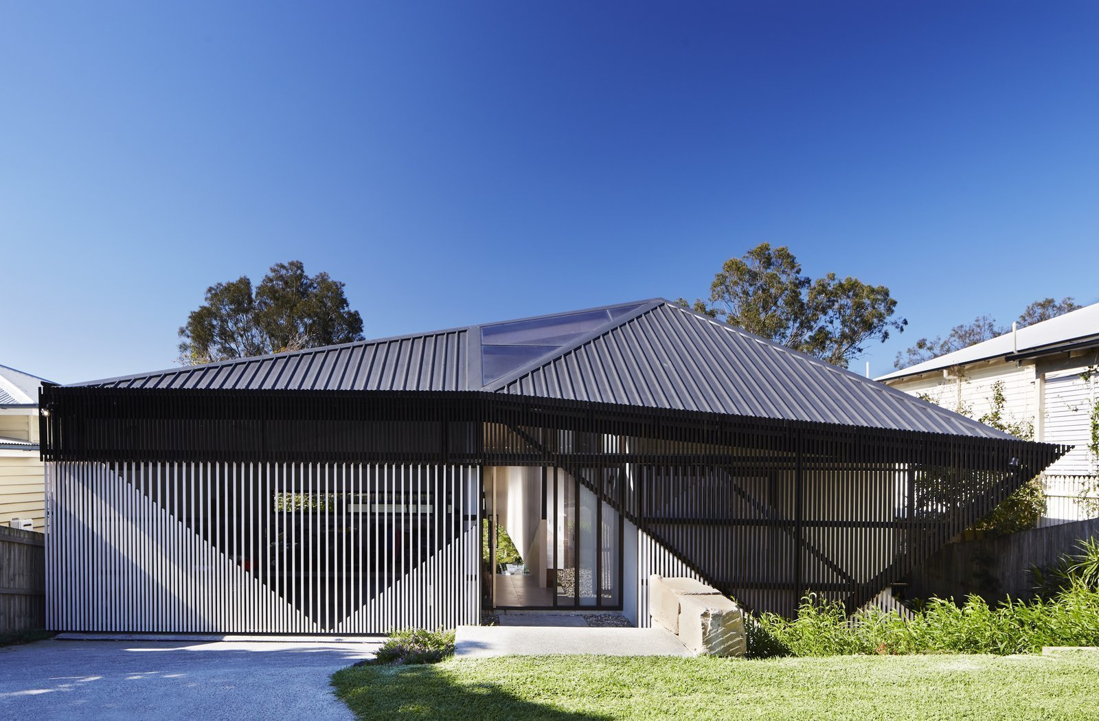Using slats with varieds widths of space between them, Bureau Proberts created a striking angular slatted façade for this Brisbane home, which reveals triangular shapes, while hinting at the life concealed within. Tagged: Exterior, Metal Roof Material, and House.  Best Photos from 9 Best Homes With Interesting Screened Facades