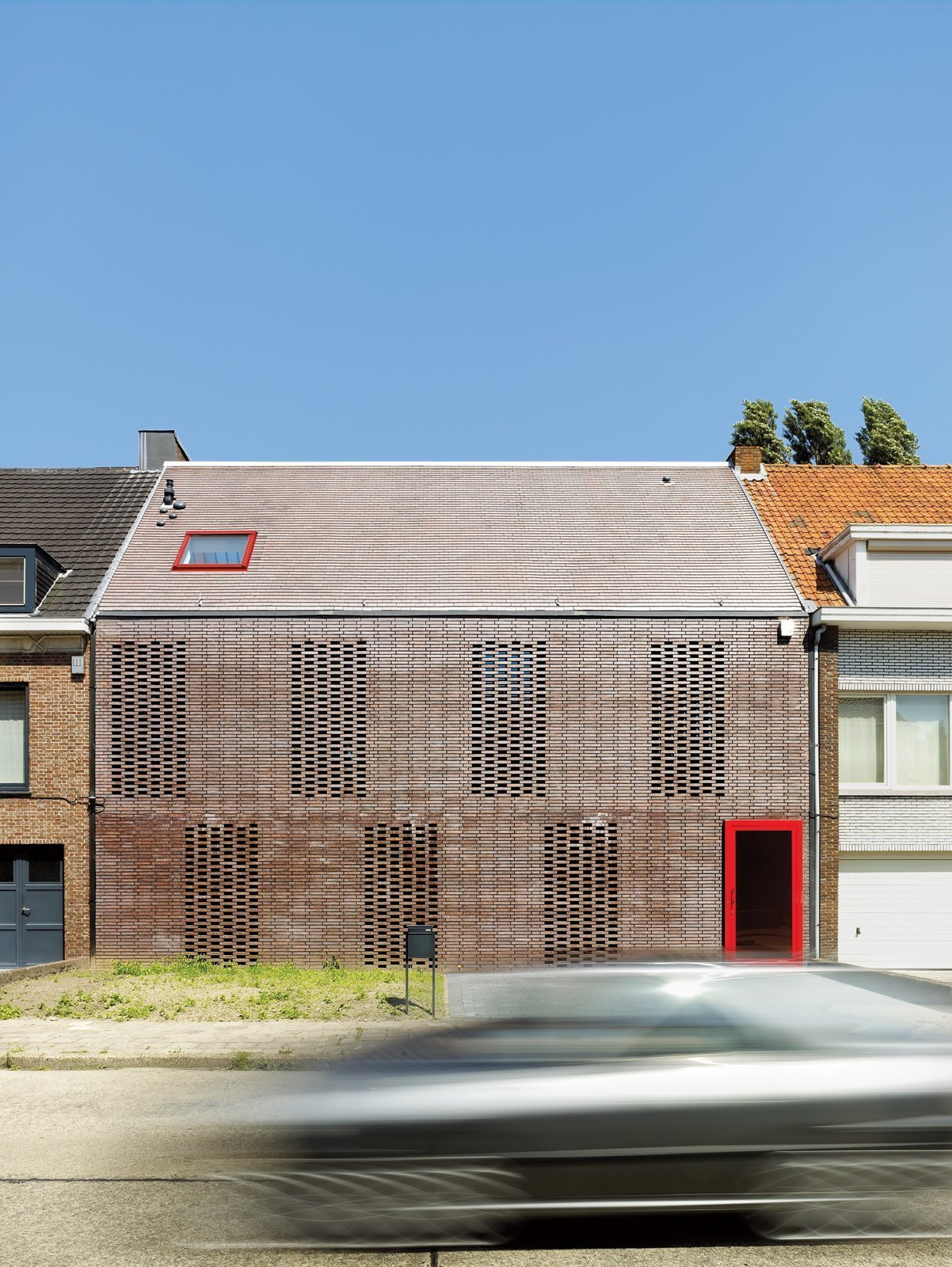 """To provide maxizing privacy and natural light penetration for their clients, Belgium-based DMVA Architects created a frontage composed of """"knitted"""" bricks, which bring light and air into the home."""