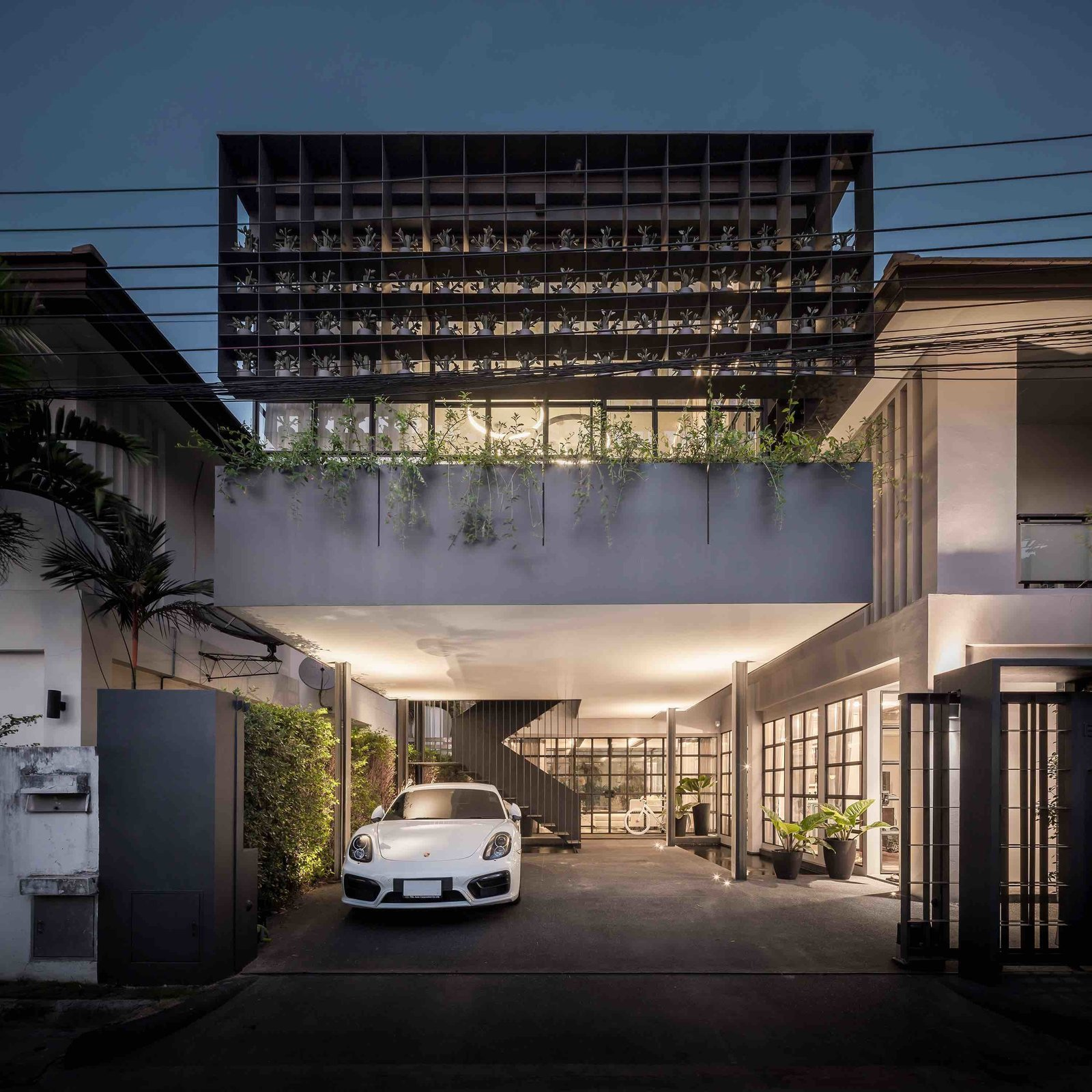 102 potted olive plants sit in the nooks of this reinforced gridded-steel framework that wraps around the front of this Bangkok home designed by Thai architecture firm Anonym Studio.
