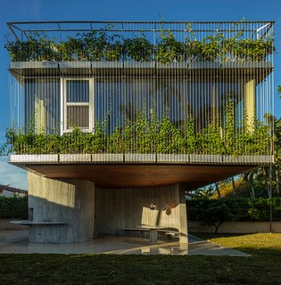9 Best Homes With Interesting Screened Facades - Photo 17 of 18 - The second level of this dining room, bedroom, and sundeck extension in Miami is clad in vine-covered metal trellises that provide the bedroom and bathroom with privacy while bringing in plenty of sunshine during the day.