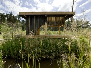 8 Japanese-Inspired Spaces We Love - Photo 3 of 8 - Named after its charred-larch cladding, this tearoom designed by Czech studio A1 Architects sits next to a lake in a woodland area near the city of Česká Lípa in the Czech Republic. Its sliding doors can be opened for enhanced connectivity with the surrounding nature, or closed to create a more secluded oasis. At the center of the space is a hearth with a teapot suspended from a sisial rope-domed ceiling above it.