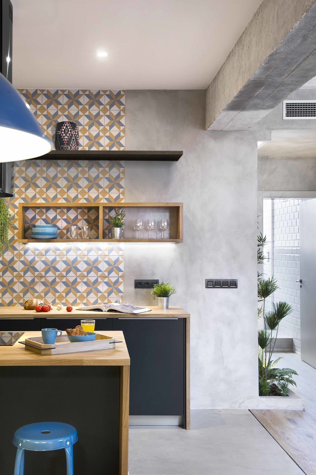 Geometric-patterned, hydraulic-imitation tiles from Portuguese brand Recer in grey, mustard, and white used for the backsplash, and a feature wall gives this Barcelona apartment plenty of vibrant charm. Tagged: Kitchen, Wood Counter, Cooktops, Medium Hardwood Floor, Concrete Floor, Ceramic Tile Backsplashe, Pendant Lighting, Recessed Lighting, and Open Cabinet.  Photo 8 of 12 in 12 Brilliant Kitchen Backsplash Ideas