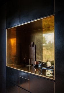 12 Brilliant Kitchen Backsplash Ideas - Photo 9 of 12 - This off-the-grid cabin in New Zealand features a kitchen niche that's lined with polished brass. It works seamlessly with a tap by Arne Jacobsen for Vola that perfectly contrasts the otherwise spare, black, and minimalist interiors.