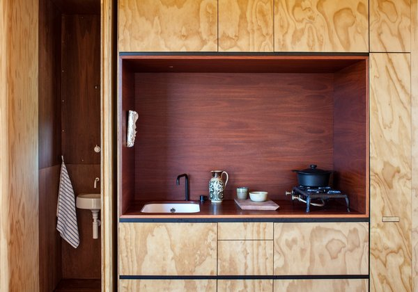 Oiled jarrah eucalyptus contrasts with a kitchen niche of reddish-brown stained plywood in this kitchen alcove in a New Zealand cabin.