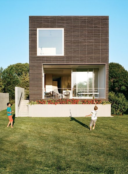 This Rhode Island home has a modernist box structure with an exterior made of milled, charred, brushed, and oiled cypress slats manufactured by Delta Millworks.