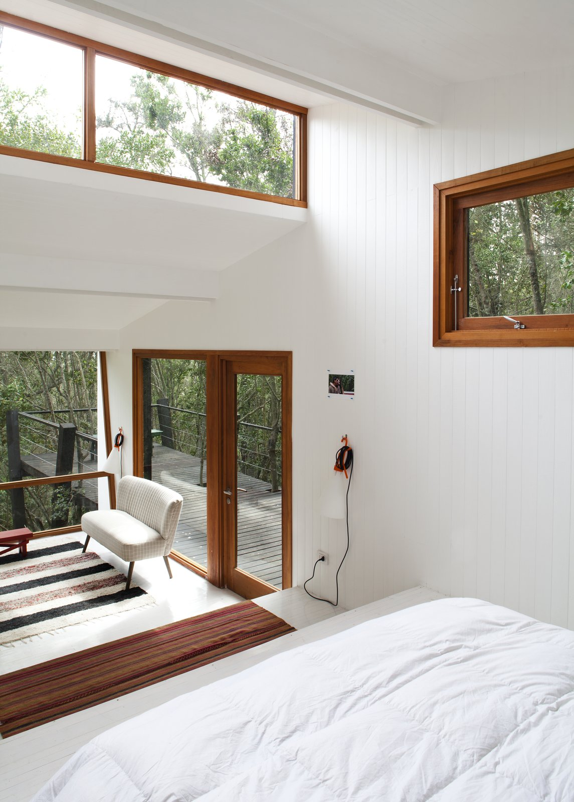 Tagged: Bedroom, Bed, Painted Wood Floor, Wall Lighting, and Rug Floor.  Best Photos from A Little Chilean Tree House That's One With the Canopy