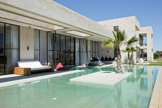 Discover 8 of the Best Mediterranean Homes - Photo 11 of 11 - Just 25 minutes from the medina of Marrakech, this contemporary Moroccan villa designed by Algerian architect Imaad Rahmouni celebrates Mediterranean living with lush gardens, an indoor/outdoor pool, retractable floor-to-ceiling windows, and a large semi-covered terrace that offers views of the Atlas Mountains.