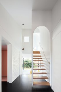 Discover 10 Impressive Spaces With Arched Windows and Doors - Photo 2 of 10 - Designed by TRIBE Studio Architects, this renovated Arts and Crafts family home in Sydney's leafy North Shore has an arched main entrance at the front of the house and a narrow floating staircase with a threshold that mimics the facade's arch.