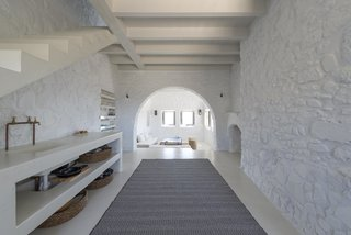 Discover 10 Impressive Spaces With Arched Windows and Doors - Photo 9 of 10 - Within this minimalist villa on the Greek island of Nisyros are vaulted ceilings, arched doorways, wood beams, white-washed walls, and clean, contemporary furnishings in white, taupe, cream, and coffee tones.
