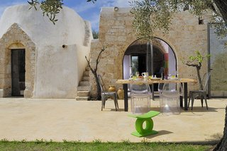 Discover 10 Impressive Spaces With Arched Windows and Doors - Photo 10 of 10 - This ancient trullo home that's been restored in the Italian commune of Ostuni in Puglia has an arched doorway that's constructed of locally harvested lime and quarried stone, which was fitted with a full-height glass door that pivots when opened and closed.