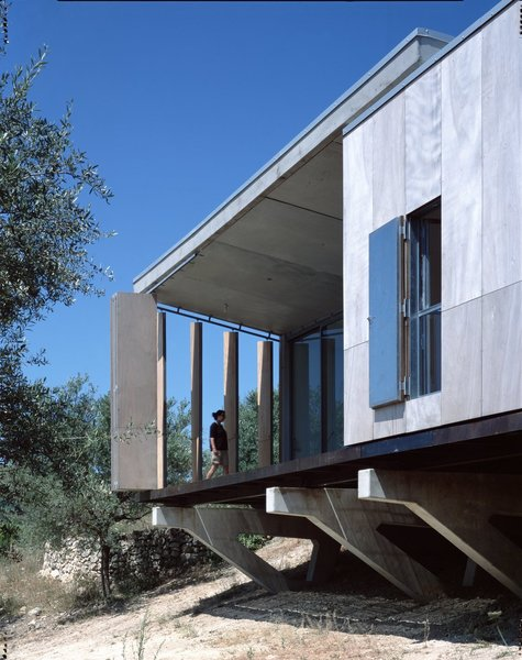 Designed by Italian architect Maria Giuseppina Grasso Cannizzo, this holiday villa in the Sicilian countryside is intelligently designed so it's raw wood board louvres can be opened to create a balcony that looks out to the countryside and sea beyond, or closed to maximize interior space.