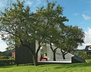 7 Homes With Beautiful Outdoor Patios - Photo 1 of 7 - This compact guesthouse in coastal Norway designed by architect Todd Saunders is defined by a wood-panel patio that's painted white and cut out from the angular, spruce-clad volume of the house. Two plum trees planted under the house grow up and through the patio.