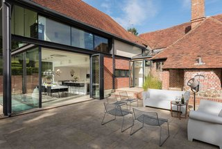 7 Homes With Beautiful Outdoor Patios - Photo 5 of 7 - A 15th-century Tudor vacation rental in Kent, England, gets a modern update with glazing and polished steel, plus a large, sun-filled patio that's furnished with contemporary outdoor furniture.