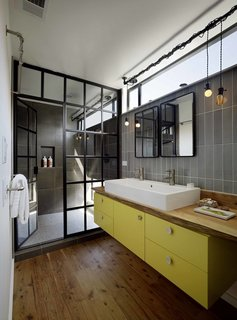 8 Bold Bathrooms That Don't Back Away From Color - Photo 7 of 9 - Even in small amounts, bright colors can uplift most bathrooms. In this Bay Area houseboat, architect Robert Nebolon used a teak live-edge countertop and a custom yellow cabinet supporting a double washbasin by Duravit to create a sophisticated steampunk-inspired look.