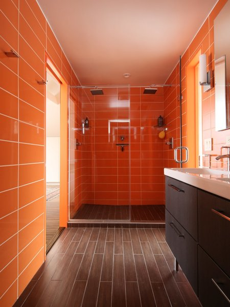Roca wall tiles in an orange hue called Rainbow Azul used a long the walls and in the shower stall of this bathroom to give it sassy midcentury vibe.
