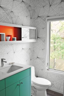 8 Bold Bathrooms That Don't Back Away From Color - Photo 9 of 9 - When upgrading this 1960s midcentury home in Austin, Texas, local architects local architects Rick and Cindy Black created a new powder room with punchy Jill Malek wallpaper, a turquoise built-in cabinet and vanity support, and a mirrored shelving unit with a back wall painted orange-red.