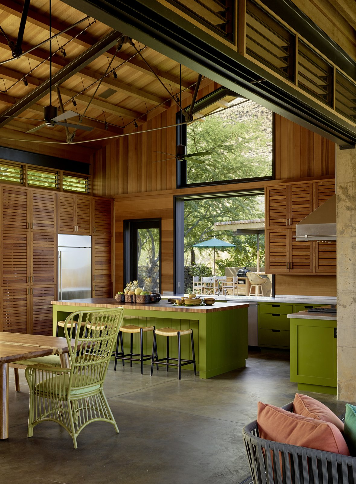 Tagged: Kitchen, Marble Counter, Wood Counter, Wood Cabinet, Concrete Floor, Range Hood, Refrigerator, Wood Backsplashe, and Track Lighting.  Photo 7 of 20 in An Incredible Home in Hawaii That's As Much Fun As Summer Camp