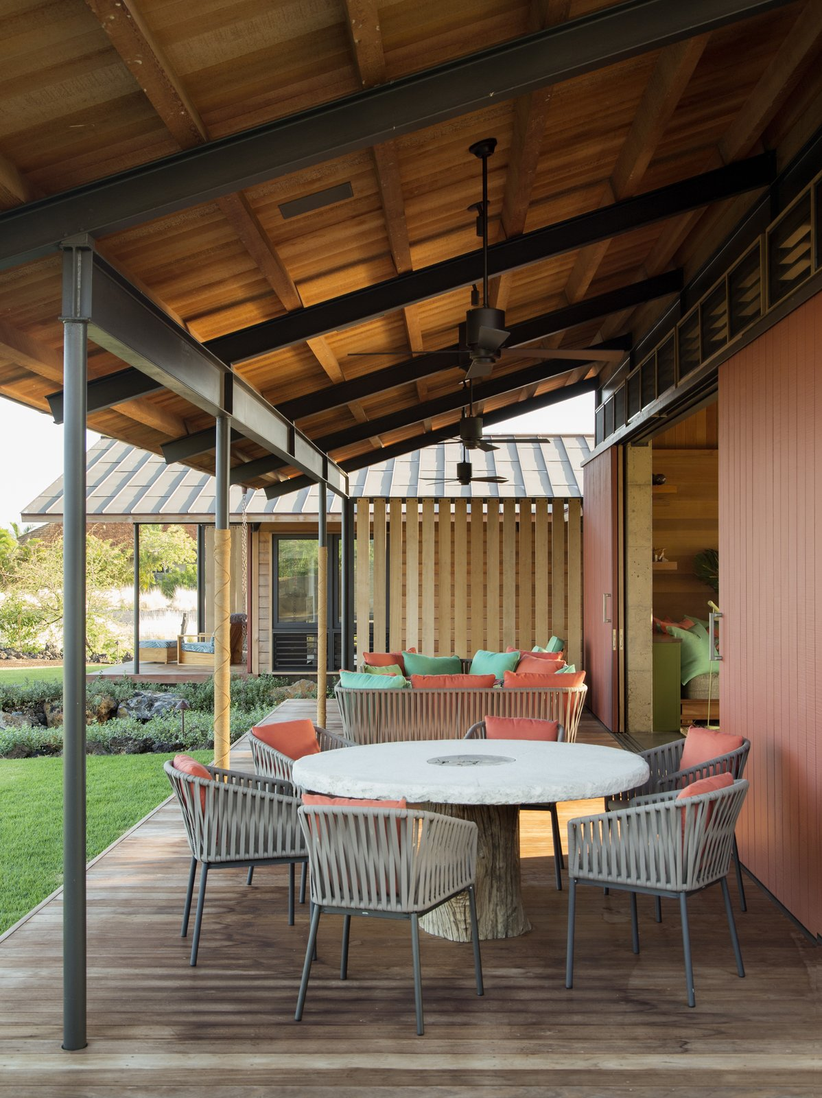 Tagged: Outdoor, Back Yard, Grass, Small Patio, Porch, Deck, Wood Patio, Porch, Deck, Decking Patio, Porch, Deck, and Hanging Lighting.  Photo 8 of 20 in An Incredible Home in Hawaii That's As Much Fun As Summer Camp