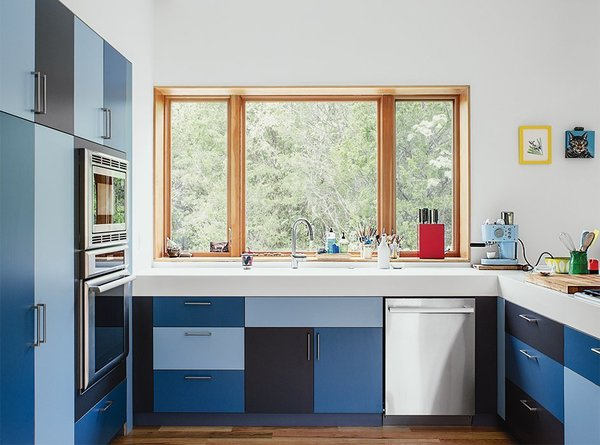 In this home near Knoxville Tennessee, the owner's friend Forrest Kirkpatrick constructed laminate Mondrian-like kitchen cabinets in three alternating shades of blue.