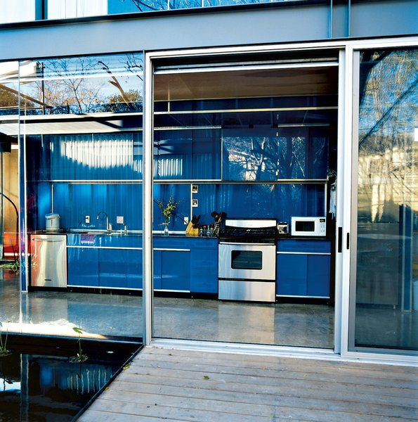 The inaugural project of Bercy Chen Studio, this home in Austin, Texas has a cobalt blue galley-style kitchen that is free from visible knobs and hinges.