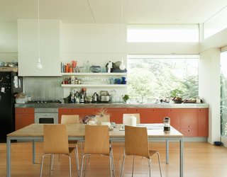 12 Electrifying Kitchens That Are Unapologetic About Color - Photo 9 of 12 - New Zealand architect Gerald Parsonson and his wife, Kate, designed their vacation beach home in Paraparaumu with an open-plan kitchen with open shelves, bar light bulbs, and bright orange MDF cabinets.
