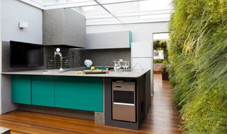 12 Electrifying Kitchens That Are Unapologetic About Color - Photo 10 of 12 - This São Paulo by Casa14 Arquitetura has plenty or large thresholds and open spaces, and a kitchen with turquoise cabinets surrounded by lush vertical green walls.