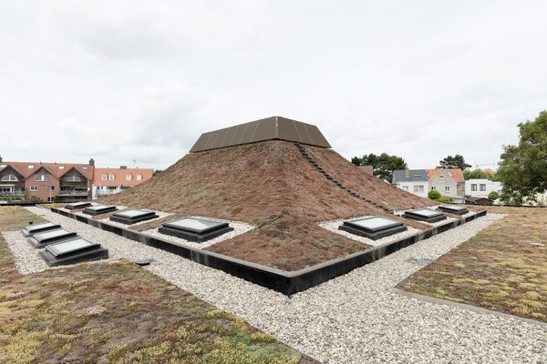 In the Belgian city of Knokke-Heist, is a school designed by Amsterdam studio NL Architects, which has a turfed pyramidal roof with curving sides atop one of the administrative offices.