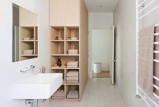 8 Bathroom Storage Hacks You Probably Haven't Tried Yet - Photo 7 of 8 - This home in Melbourne by design duo Kathryn Robson and Susie Cohen has deep nook shelves at one end of the wardrobe, which gives the bathroom a warm, natural, and organic feel.