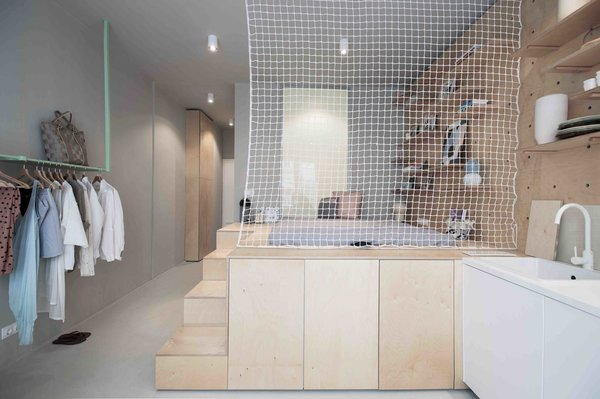 """To maximize space in this tiny 323-square-foot studio Budapest apartment, local design studio POSITION Collective used an elevated, plywood sleeping unit inspired by Japanese """"tansu"""" mobile cabinetry, with secrete storage modules on the side of the steps leading up to the futon bed."""