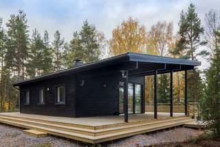 These Log Cabin Kit Homes From Finland Are Surprisingly Sleek - Photo 8 of 15 - Available in sizes that range from 646 to 850 square feet, this model has a sheltered terrace at one end that's great for outdoor barbecues or a summer kitchen.