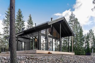These Log Cabin Kit Homes From Finland Are Surprisingly Sleek - Photo 10 of 15 - Iniö has a high-ceilinged terrace, and is fitted with generous floor-to-ceiling windows in the living room and dining area that bring in plenty of natural light.