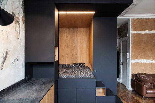 """A """"space cube"""", made of Fenix NTM's matte nanotech material combined with warm oak serves as sleeping nook and storage."""