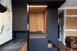 """A Multipurpose Bedroom Box Is This Tiny Apartment's Genius Solution - Photo 2 of 8 - A """"space cube"""" made of Fenix NTM's matte nanotech material and warm oak serves as a sleeping nook and storage."""