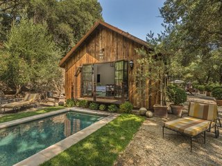 7 Modern Farmhouses to Rent For the Most Picturesque Vacation Ever - Photo 6 of 7 - This Napa Valley farmhouse in Saint Helena has a pool, and an outdoor dining area with a fountain and a rock fireplace.